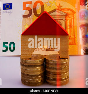 model of a wooden house sits on piles of euro coins on the background of a fifty euro banknote. Closeup. Currency - Stock Photo