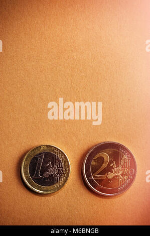 coins one and two euros on a background of cardboard. Closeup. Currency of the Euro Union. - Stock Photo