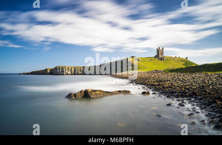Dunstanburgh Castle from the north bay showing the Lilburn Tower and Greymare rocks, Northumberland, England - Stock Photo