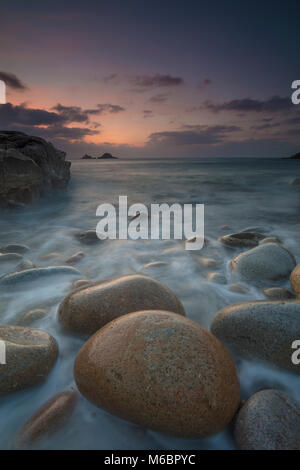 Boulders on Porth Nanven beach looking towards the Brisons at sunset Cot Valley near St Just Cornwall - Stock Photo