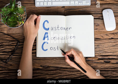 Elevated View Of A Businessperson Writing Customer Acquisition Cost Concept On Notebook - Stock Photo