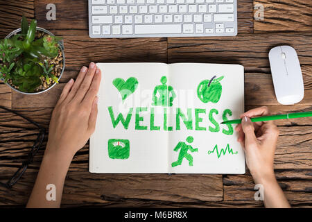 High Angle View Of A Human Hand Drawing Wellness Concept On Notebook - Stock Photo