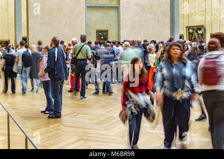 PARIS - MAY 16: Unidentified huge group of tourist taking photos to Mona Lisa at the Louvre Museum on May 16 2015 - Stock Photo