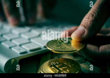closeup of a young man having a bitcoin from a pile of bitcoins while is using a computer, with a dramatic effect - Stock Photo