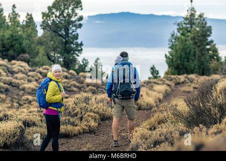 Couple hiking with baby boy travelling in backpack. Hikers family, adventure with child on autumn family trip in - Stock Photo