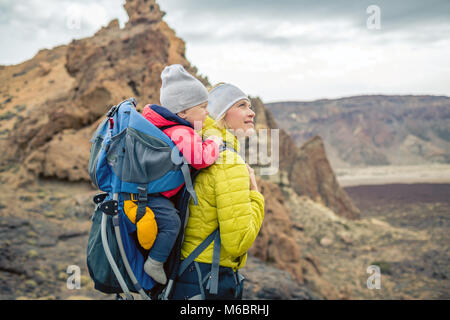 Family hike baby boy travelling in mother's backpack. Hiking adventure with child on autumn family trip in mountains. - Stock Photo