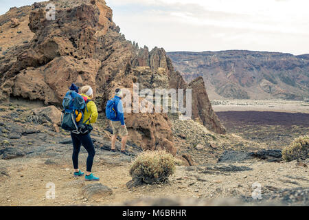 Family hiking with baby boy travelling in backpack. Hiking adventure with child on autumn family trip in mountains. - Stock Photo