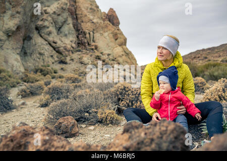 Happy mother with little boy travelling in mountains. Hiking and camping adventure with child on autumn family trip. - Stock Photo
