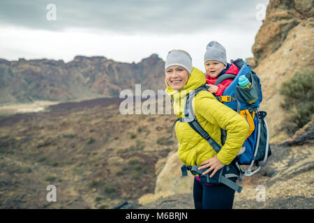 Happy mother with little boy travelling in backpack. Hiking adventure with child on autumn family trip in mountains. - Stock Photo