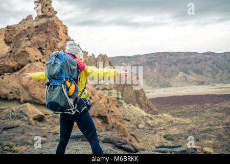 Super mom with baby boy travelling in backpack. Hiking adventure with child on autumn family trip in mountains. - Stock Photo