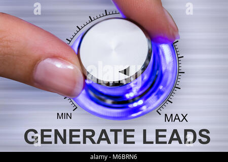 Close-up Of A Person's Hand Turning Generate Leads Concept - Stock Photo