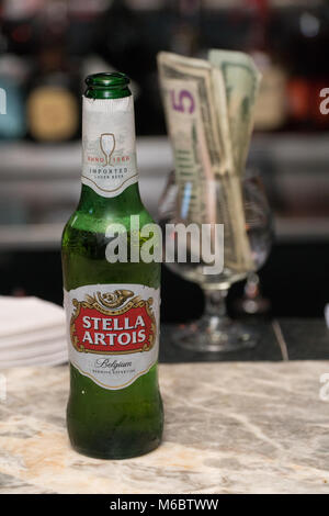 New York, Circa 2018: Stella Artois beer bottle on restaurant bar counter top. Alcohol served to customers by bartender. - Stock Photo