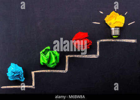 Evolving idea concept with colorful crumpled paper and light bulb on steps drawn on blackboard. - Stock Photo