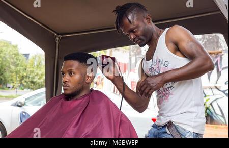 Man having haircut in an informal barber shop in Johannesburg. - Stock Photo
