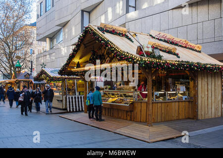 Shoppers and Christmas market food stalls in city centre pedestrianised street. Munich, Bavaria, Germany, Europe - Stock Photo