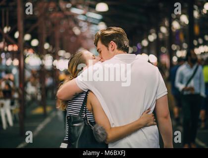 Happy couple kissing in Queen Victoria Market, Australia. - Stock Photo