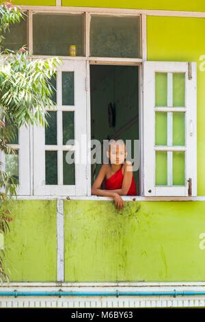 Young novice monk looking out of window at Aung Myae Oo Monastic Free Education School, Sagaing, Mandalay, Myanmar - Stock Photo