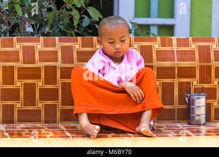 Young novice monk sitting on seat at Aung Myae Oo Monastic Free Education School, Sagaing, Mandalay, Myanmar (Burma), - Stock Photo