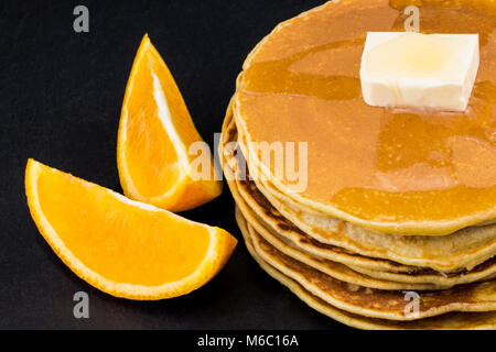 Stack of pancakes in syrup with oranges on dark background. - Stock Photo