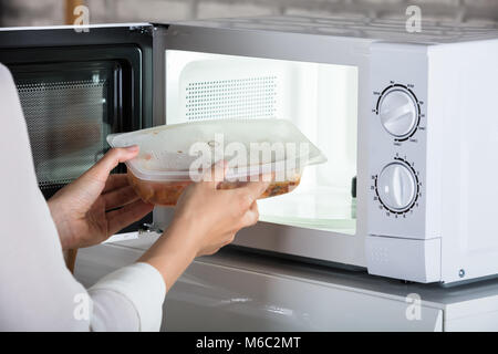 Close-up Of A Person Removing Prepared Food From Microwave Oven - Stock Photo