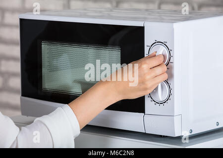 Woman Using Microwave Oven For Heating Food At Home - Stock Photo