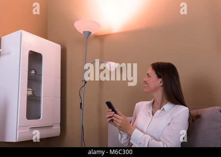 Happy Smiling Woman Controlling Electric Lamp With Mobile Phone At Home - Stock Photo