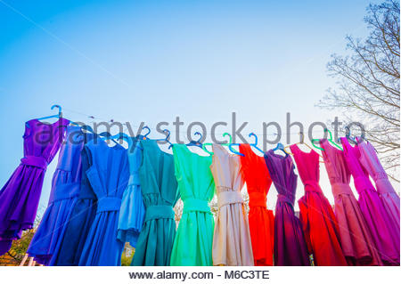 Children's Colourful dance dresses on a washing line in the late afternoon winter sun. 14 Rainbow coloured hand - Stock Photo