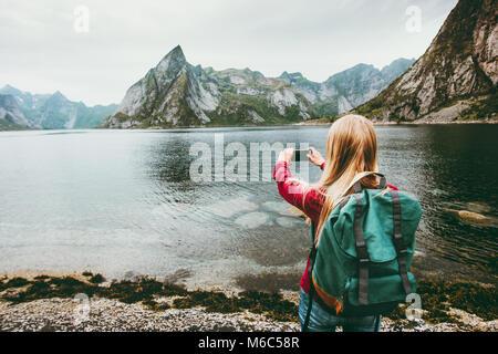 Girl tourist taking photo by smartphone sightseeing Lofoten islands Travel lifestyle wanderlust concept adventure - Stock Photo