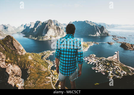Traveler Man standing on cliff edge alone traveling in Norway lifestyle adventure outdoor summer vacations Reinebringen - Stock Photo