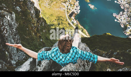Traveler Man happy raised hands sitting on cliff edge traveling in Norway lifestyle adventure outdoor extreme vacations - Stock Photo
