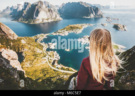 Blonde woman on the top of Reinebringen mountain fjord aerial view in Lofoten islands of Norway Travel backpacking - Stock Photo