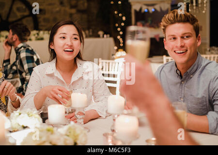 Wedding guests are socialising at the dinner party. - Stock Photo