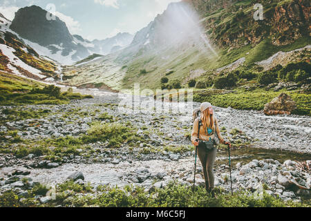 Woman backpacker hiking in mountains adventure travel lifestyle concept active summer vacations sport outdoor - Stock Photo