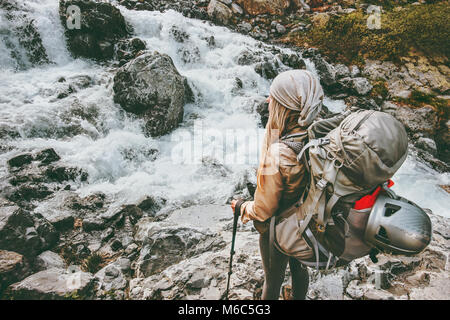 Adventurer travel woman hiking with backpack at river in mountains healthy lifestyle concept active summer vacations - Stock Photo