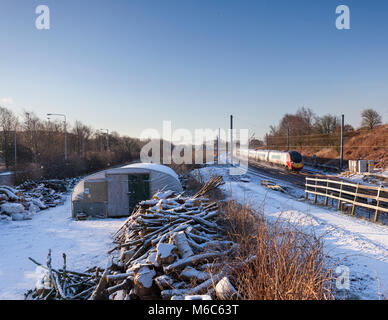 A Virgin Trains west coast pendolino train in the snow  on the west coast main line near Lancaster - Stock Photo