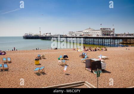 BRIGHTON, UK - JUN 5, 2013: Holidayers enjoying good summer weather at shingle beach near the Brighton Palace Pier - Stock Photo
