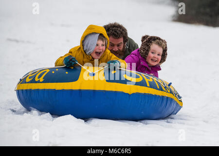 Phil Rogers and kids Rocco and Ruby sledge using an inflatable dinghy in Batheaston in Somerset after heavy snowfall. - Stock Photo