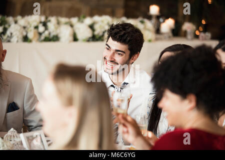 A table of happy wedding guests are socialising as they wait for the starters of their meal. - Stock Photo