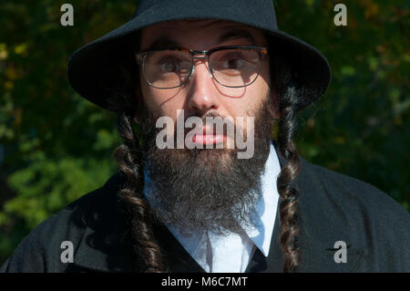 Outdoor sunny portrait of bewildered young strange looking orthodox Jewish man with black beard and hat wearing - Stock Photo