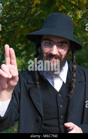 Sunny outdoor portrait of a young smiling happy fingers blessing traditional orthodox Jewish man with black beard - Stock Photo