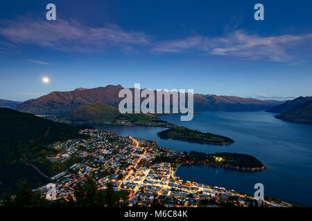 A full moon rises over Lake Wakatipu, Queenstown, New Zealand - Stock Photo