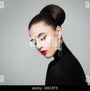 Elegant Young Woman with Hair Bun Hairstyle and Eyeliner Make up. Female Model wearing Black Roll Neck Jumper. - Stock Photo