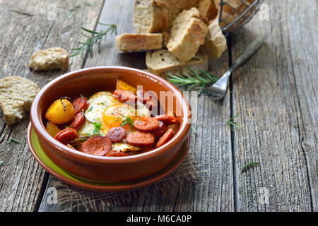 Spanish tapa: Spicy chorizo sausage with fried egg and baby potatoes served in a terra cotta cazuela dish - Stock Photo