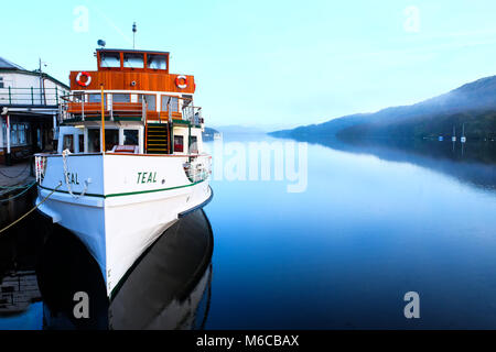 white and wooden vintage Steam ferry moored on lake Windermere, Lake District, UK, early morning view across the - Stock Photo
