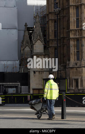 A construction worker wheels materials towards renovated parts of the Houses of Parliament, Whitehall, London, United - Stock Photo