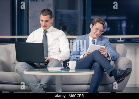 Two young businessmen sitting in office lobby and using laptop and digital tablet device - Stock Photo