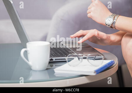 Close up of female hands using laptop keyboard. Cup of coffee, notebook and eyeglasses next to computer. Business - Stock Photo