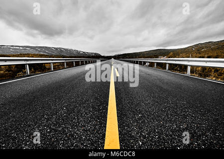 image of a wide open prairie and mountains with a paved highway road stretching out as far as the eye can see with - Stock Photo