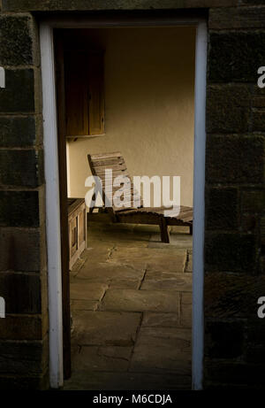 A slatted wooden sun lounger can be seen through a doorway at York Gate Garden, Adel, Leeds - Stock Photo