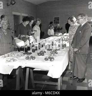 1960s, historical, visitors to a church fundraising fete study the home-made jams, cakes and fruit on display inside, - Stock Photo